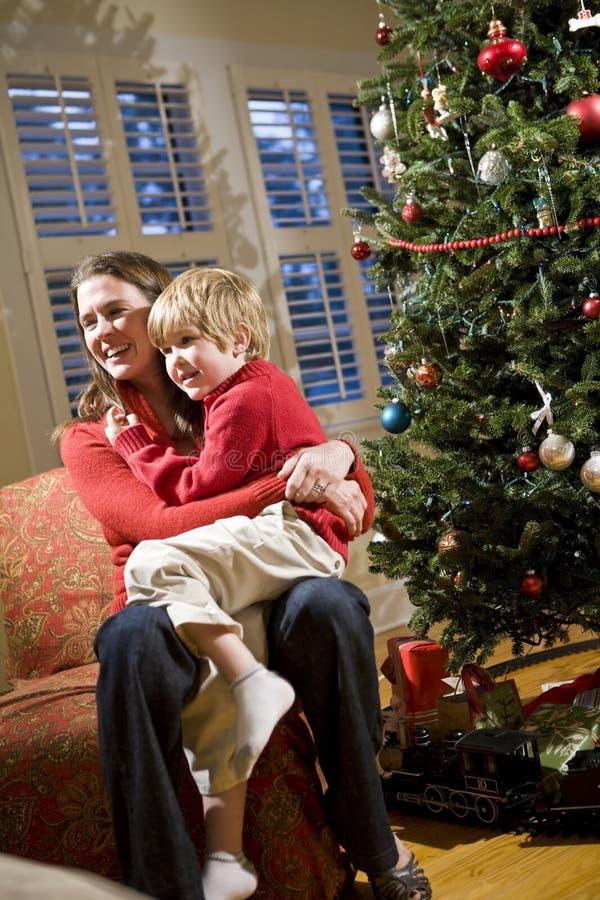 Madre e hijo joven que se sientan por el árbol de navidad imagenes de archivo