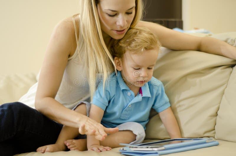 Madre e hijo jovenes con una tableta fotografía de archivo