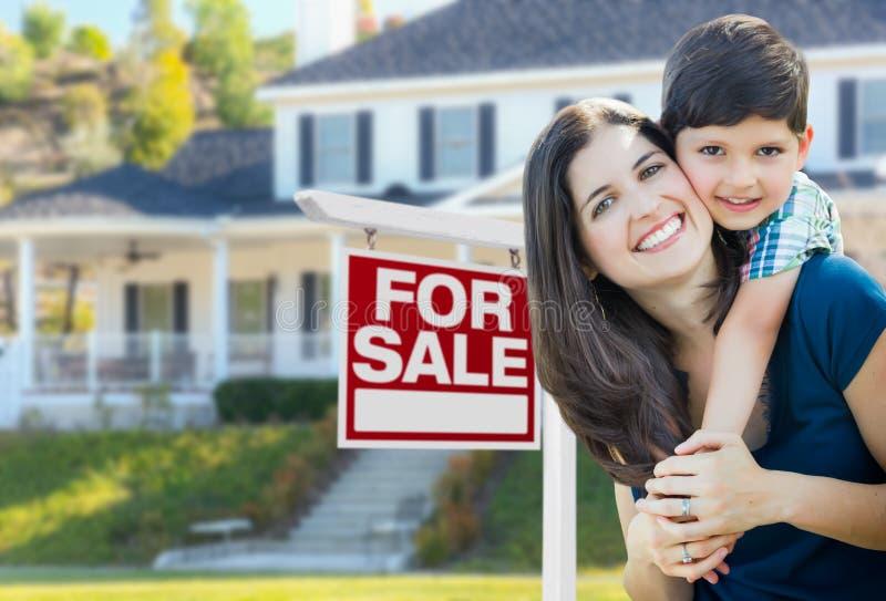 Madre e hijo jovenes delante para de la muestra y del hogar de Real Estate de la venta foto de archivo libre de regalías