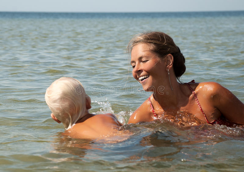 Madre e hijo jovenes en el mar foto de archivo