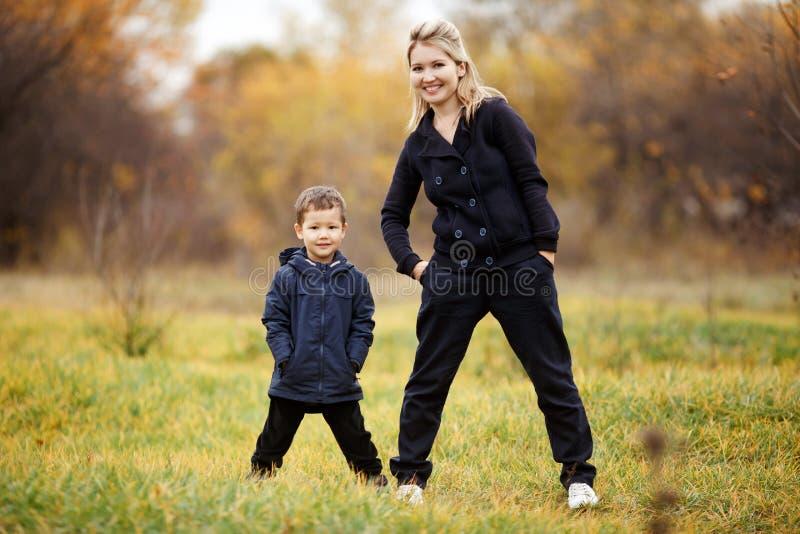 Madre e hijo jovenes en el otoño Forest Park, follaje amarillo ropa de sport Niño que lleva la chaqueta azul Familia incompleta imagenes de archivo