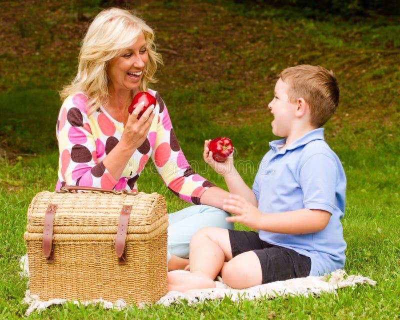 Madre e hijo que disfrutan de comida campestre al aire libre imágenes de archivo libres de regalías