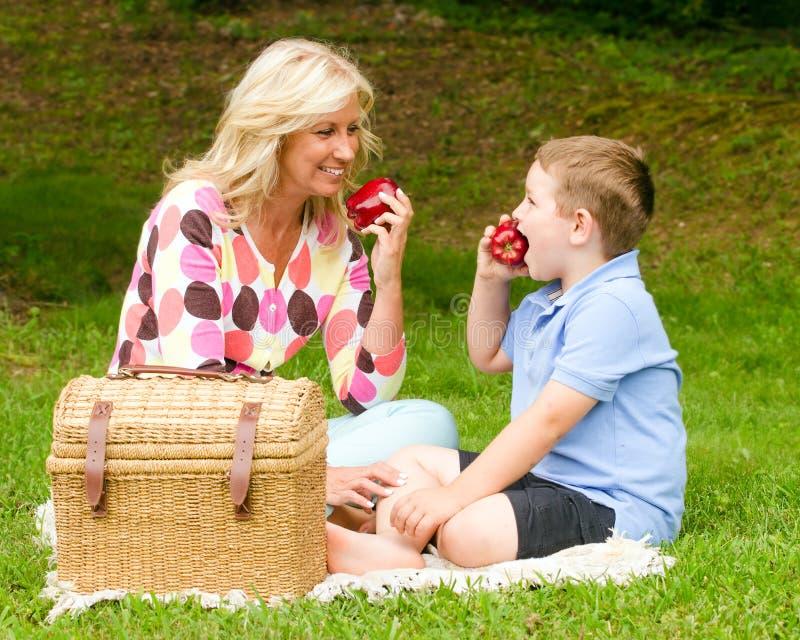 Madre e hijo que disfrutan de comida campestre al aire libre fotos de archivo