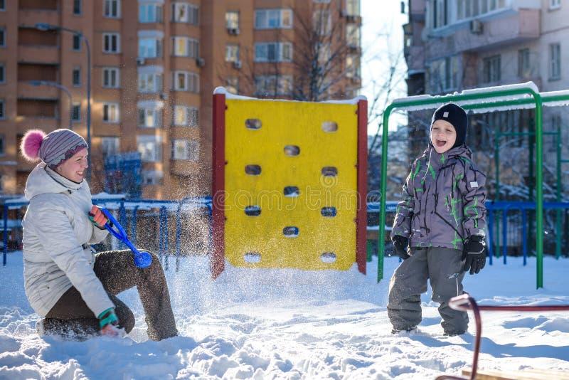 Madre e hijo que disfrutan de día de invierno hermoso al aire libre, jugando con nieve en ciudad imagen de archivo libre de regalías