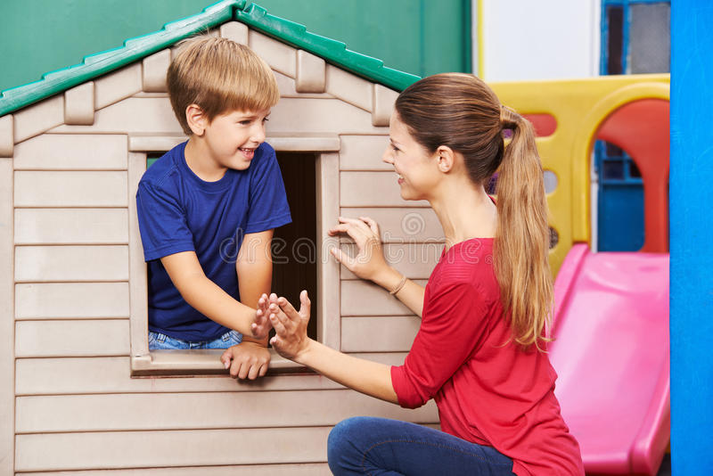Madre e hijo que juegan al juego que aplaude en cuarto de niños imagen de archivo