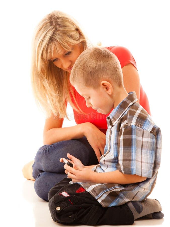 Madre e hijo que juegan al videojuego en smartphone imágenes de archivo libres de regalías