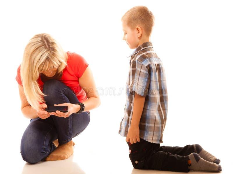Madre e hijo que juegan al videojuego en smartphone foto de archivo