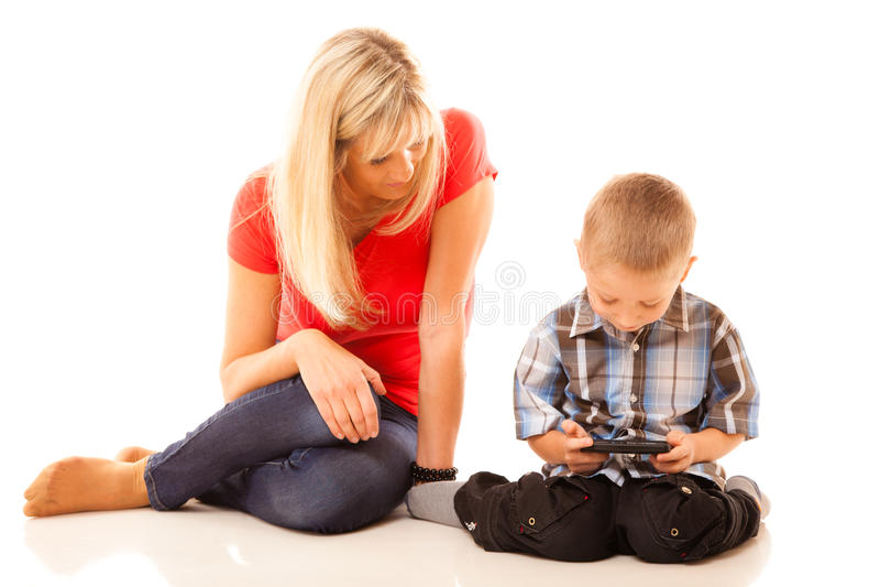 Madre e hijo que juegan al videojuego en smartphone fotografía de archivo
