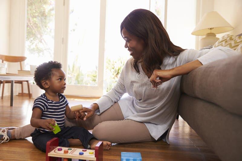 Madre e hijo que juegan con los juguetes en piso en casa imágenes de archivo libres de regalías