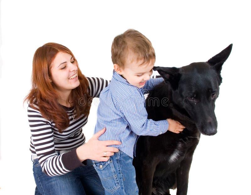 Madre e hijo que juegan con un perro imagen de archivo libre de regalías