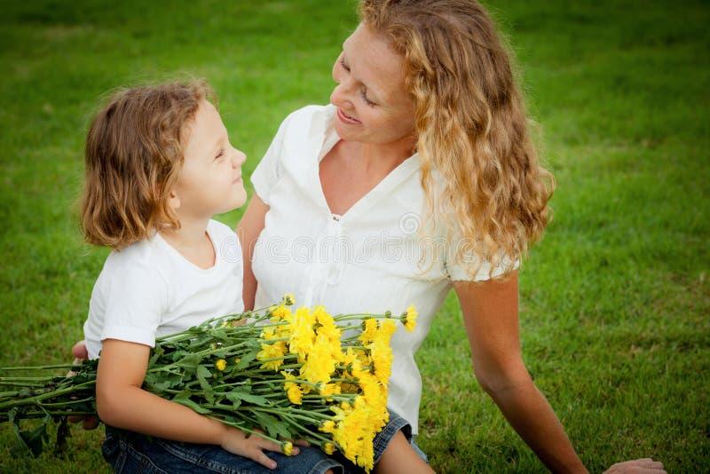 Madre e hijo que juegan en la hierba en el tiempo del día imágenes de archivo libres de regalías
