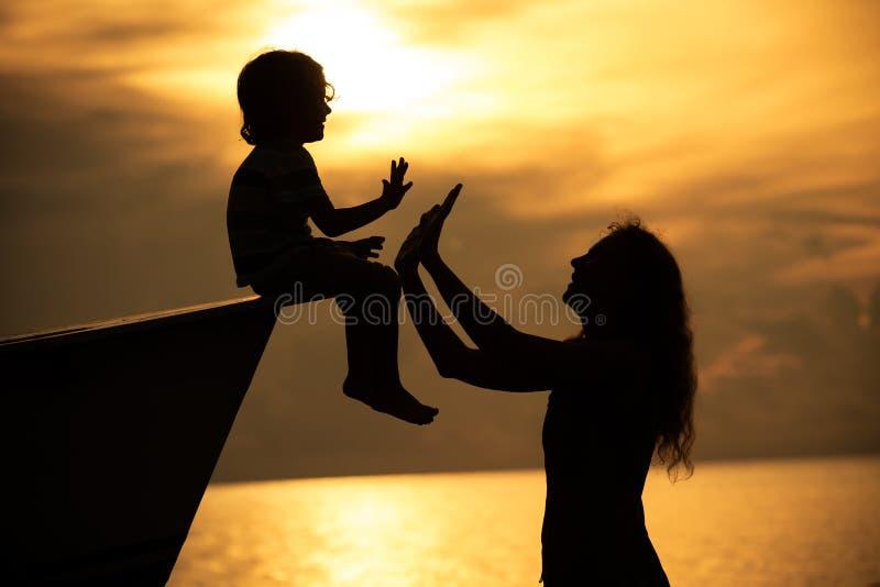 Madre e hijo que juegan en la playa imagenes de archivo
