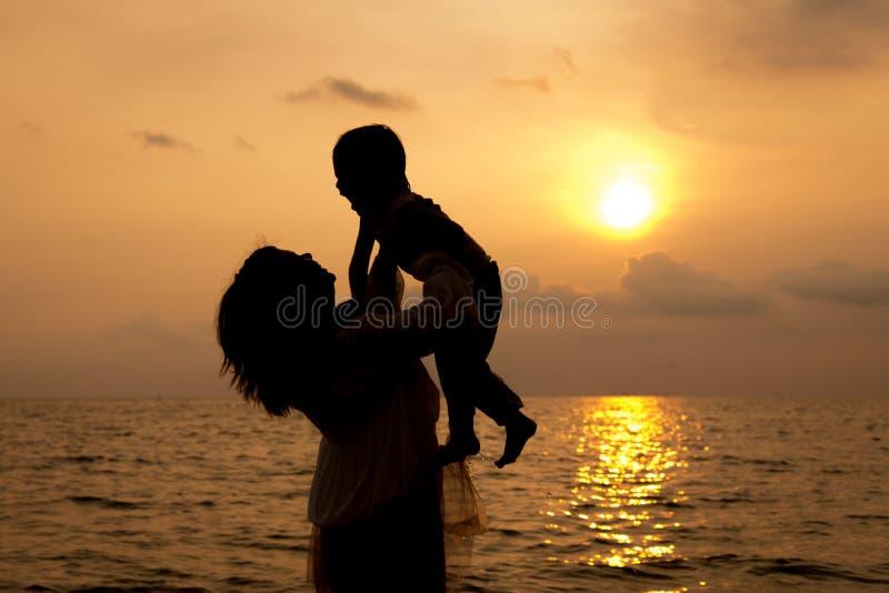 Madre e hijo que juegan en la playa en tiempo del amanecer fotos de archivo libres de regalías