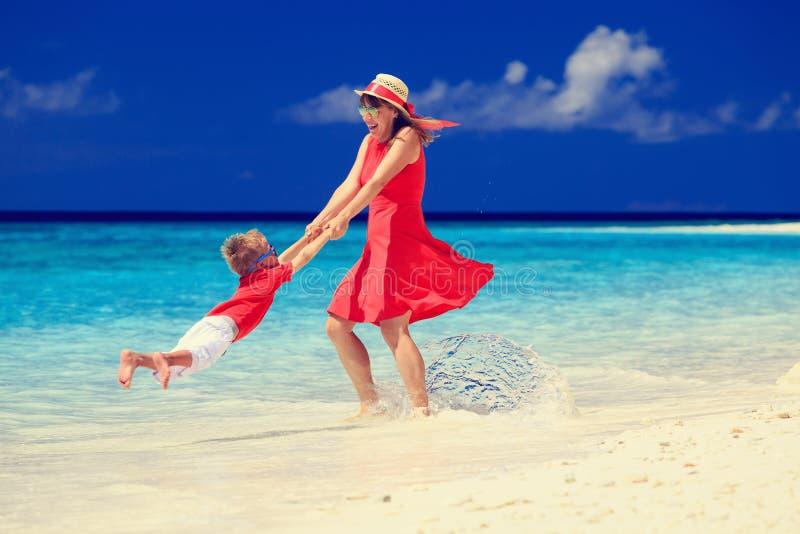 Madre e hijo que juegan en la playa tropical imagen de archivo