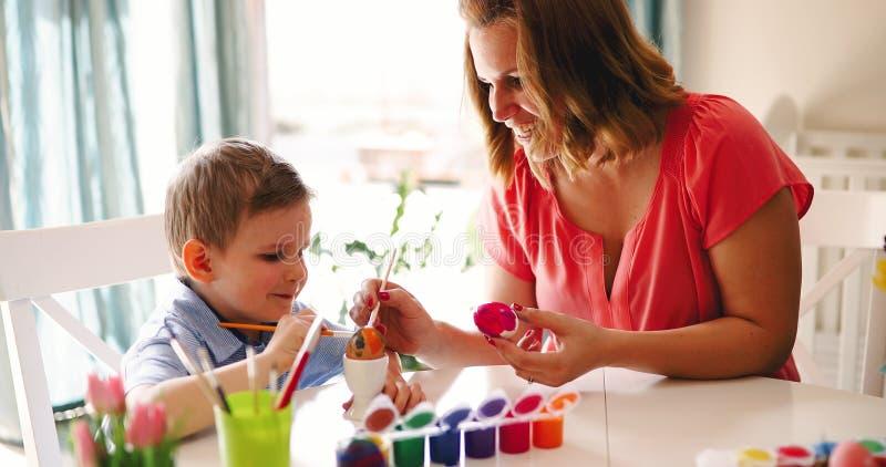 Madre e hijo que pintan los huevos de Pascua fotos de archivo