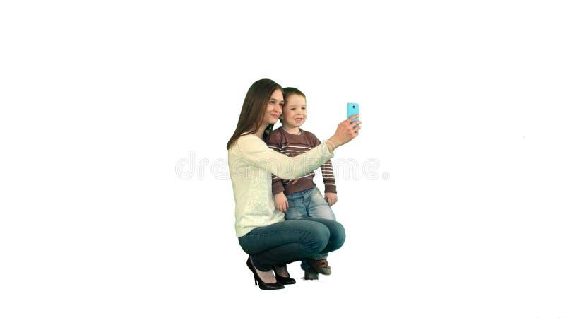 Madre e hijo que presentan para Selfie en el fondo blanco aislado fotos de archivo