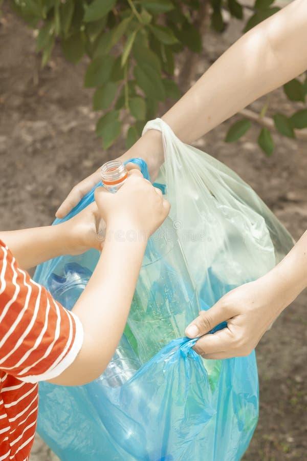 Madre e hijo que recogen las botellas plásticas La familia lleva el bolso de basura Contaminaci?n pl?stica en tierra fotos de archivo