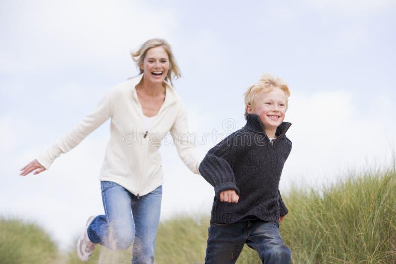 Madre e hijo que se ejecutan en la sonrisa de la playa imagen de archivo