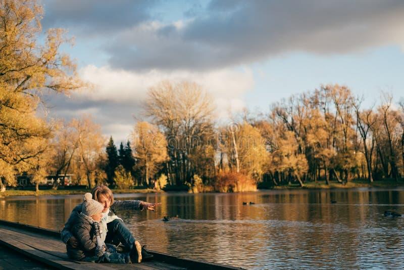 Madre e hijo que se sientan cerca del lago en parque del otoño en puesta del sol y que miran lejos La familia que se divierte, ab foto de archivo