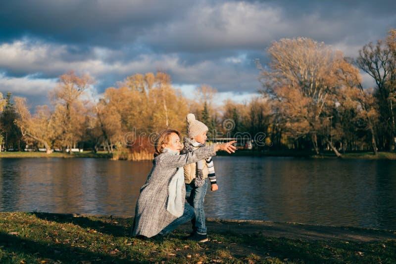 Madre e hijo que se sientan cerca del lago en parque del otoño en puesta del sol y que miran lejos La familia que se divierte, ab imagen de archivo libre de regalías