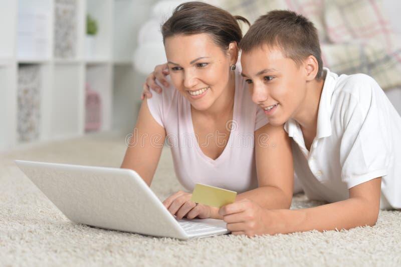 Madre e hijo que usa la computadora portátil fotos de archivo