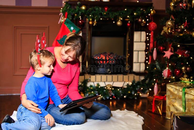 Madre e hijo que usa la PC de la tableta por una chimenea fotos de archivo