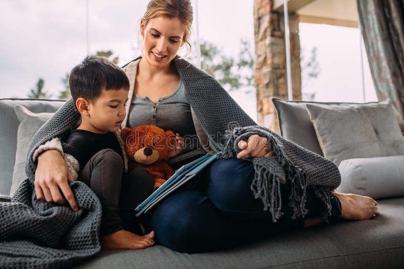 Madre e hijo que usa la tableta digital en sala de estar fotografía de archivo