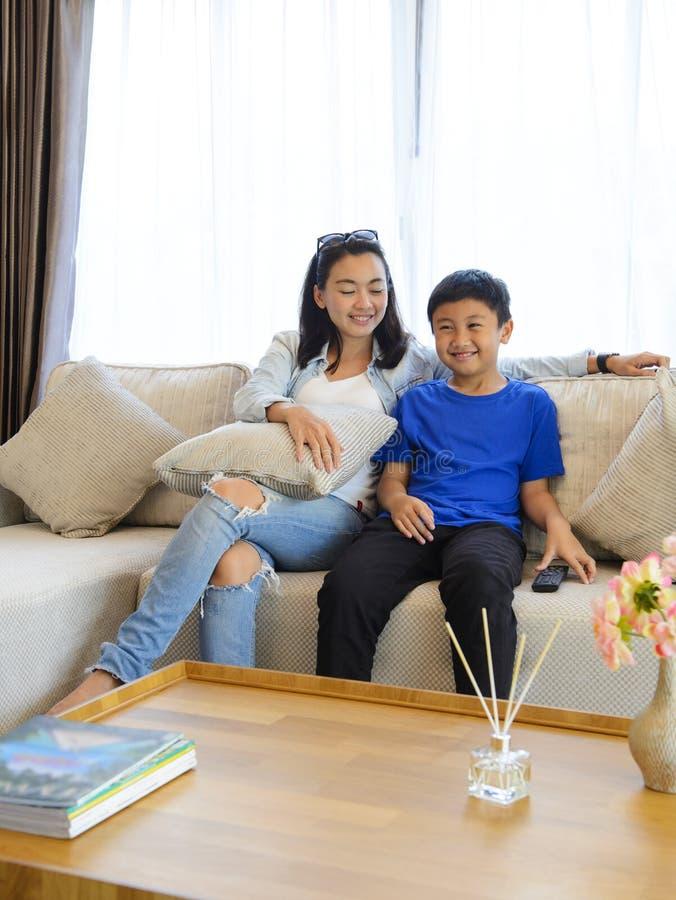 Madre e hijo que ven la TV junto en casa fotos de archivo