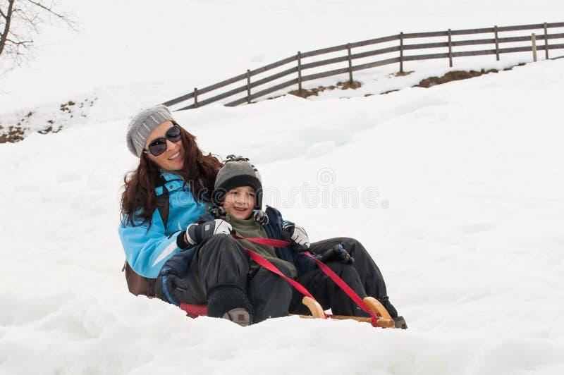 Madre e hijo sledging imagen de archivo
