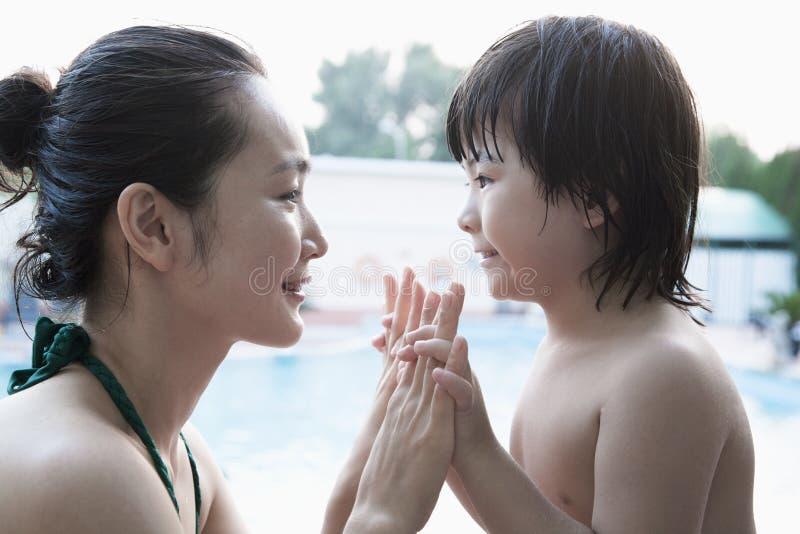 Madre e hijo sonrientes cara a cara y llevar a cabo las manos por la piscina imagenes de archivo