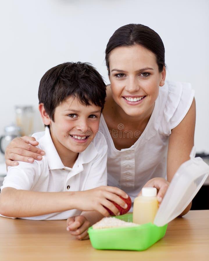 Madre e hijo sonrientes que hacen el almuerzo de escuela foto de archivo libre de regalías