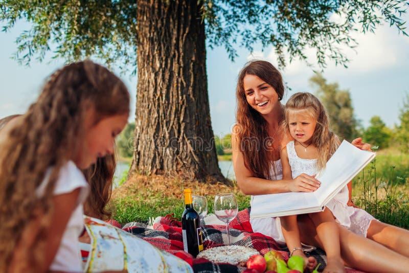 Madre e hijos leyendo libros al aire libre Familia tomando un picnic en el parque al atardecer foto de archivo