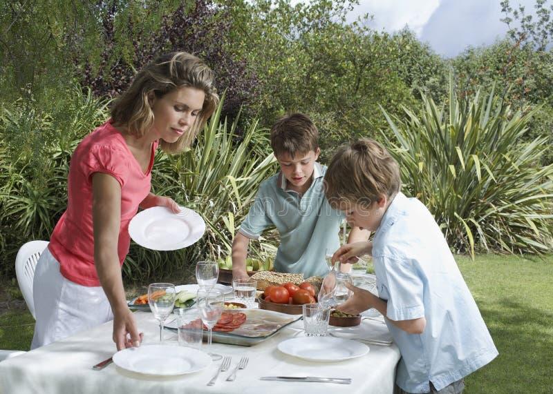 Madre e hijos que fijan la tabla de cena al aire libre fotos de archivo libres de regalías