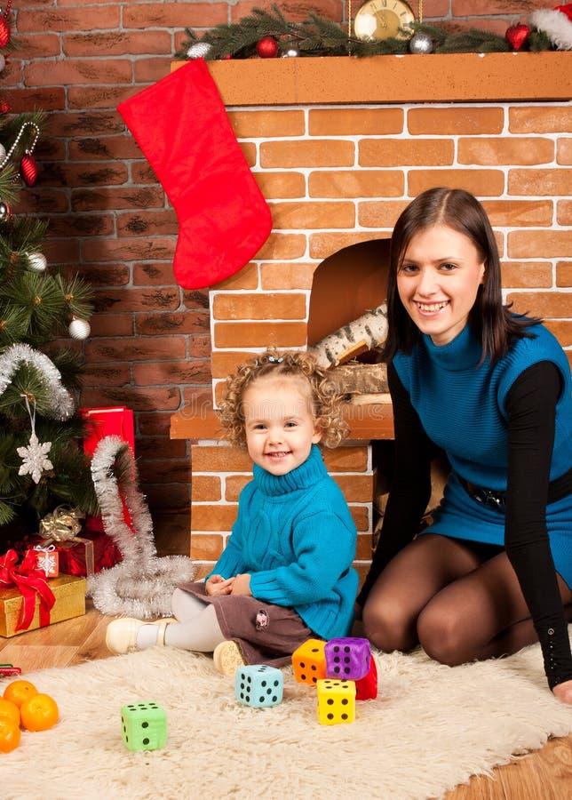 Madre e la sua figlia vicino all'albero di Natale fotografia stock