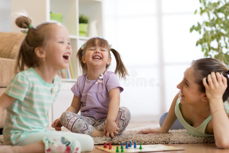 Madre e le sue figlie che giocano in gioco da tavolo immagine stock libera da diritti
