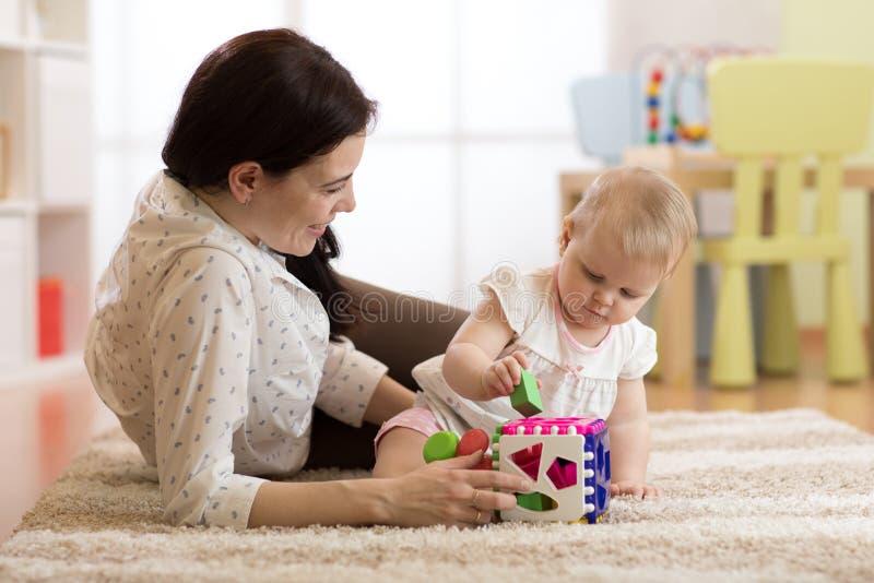 Madre e neonata che giocano con i giocattoli inerenti allo sviluppo nella stanza della scuola materna immagine stock