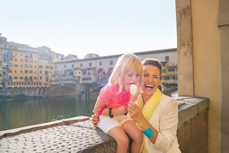 Madre e neonata che mangiano il gelato vicino al ponte v fotografia stock libera da diritti