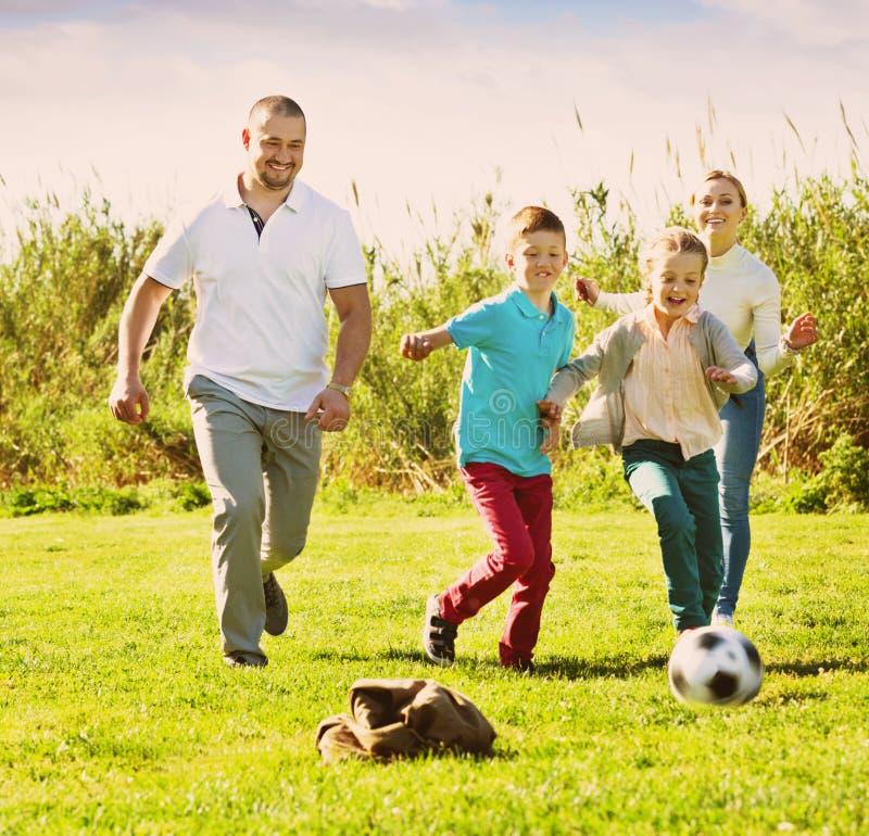 Madre e padre con due bambini che corrono dopo la palla fotografia stock