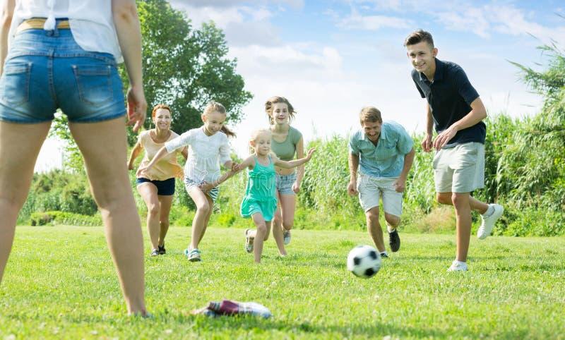 Madre e padre con i bambini felici che corrono nel parco fotografia stock libera da diritti