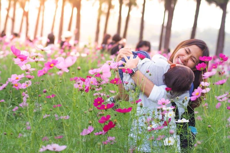 Madre e piccola figlia che giocano insieme in fiore immagini stock libere da diritti