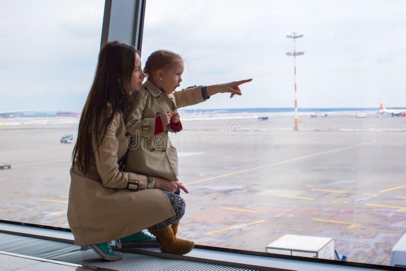 Madre e piccola figlia che guardano fuori la finestra immagine stock libera da diritti