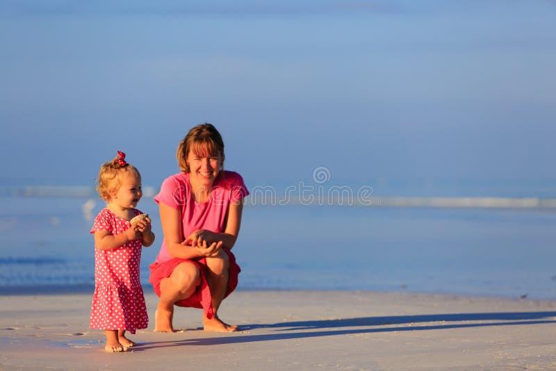 Madre e piccola figlia che raccolgono le coperture sopra fotografia stock libera da diritti