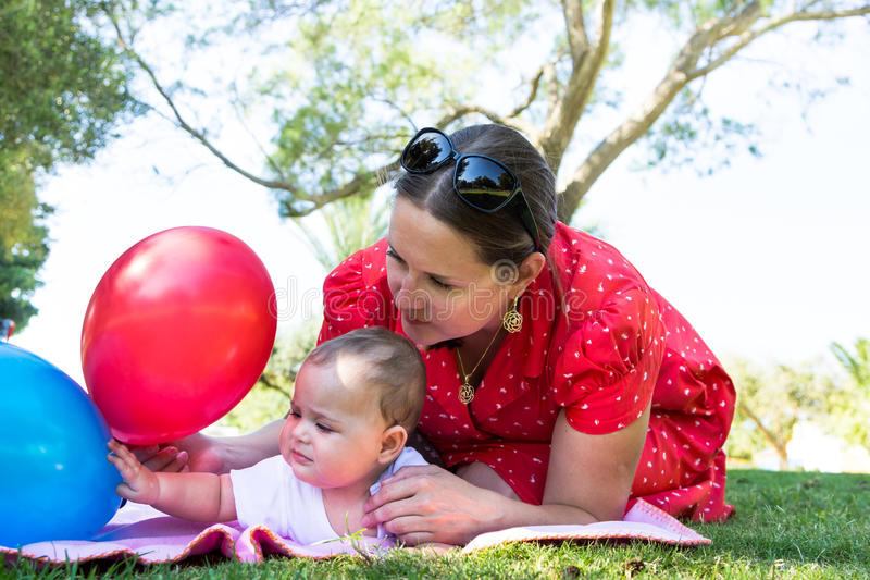 Madre e piccola neonata sveglia sul prato immagini stock libere da diritti