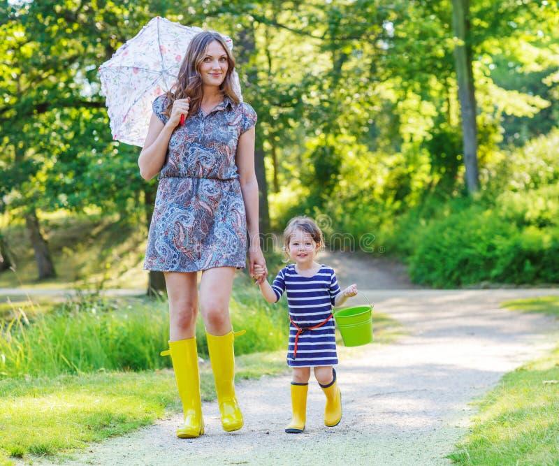 Madre e piccolo bambino adorabile in stivali di gomma gialli fotografie stock