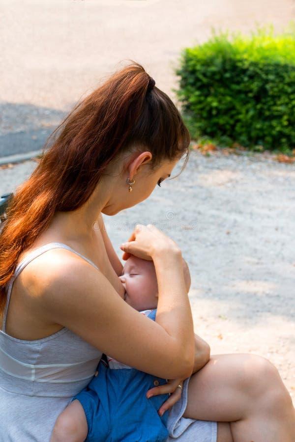 Madre e piccolo bambino che hanno tempo fuori, giovane mamma che allatta al seno il suo bambino affamato sveglio in pubblico fotografie stock