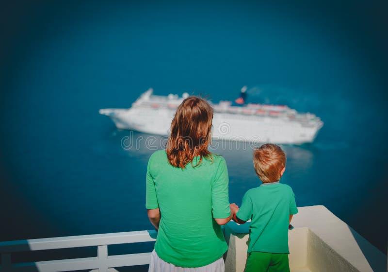 Madre e piccolo figlio che esaminano nave da crociera in mare, Santorini, Grecia immagine stock