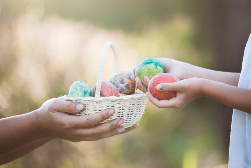 Madre e ragazza asiatica del bambino che giocano e che raccolgono l'uovo di Pasqua fotografie stock