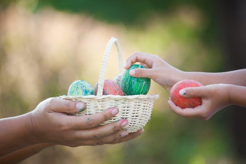 Madre e ragazza asiatica del bambino che giocano e che raccolgono l'uovo di Pasqua immagine stock