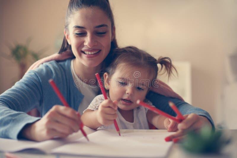 Madre e ragazza felice che giocano insieme e che scrivono immagine stock
