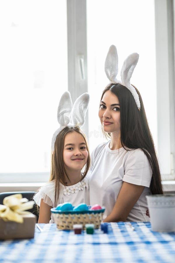 Madre e sua figlia con le uova della pittura La famiglia felice celebra Pasqua Orecchie d'uso del coniglietto della ragazza svegl fotografia stock libera da diritti